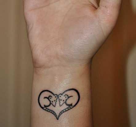 Tatuagem no pulso da menina - dois cliques do mouse em forma de coração