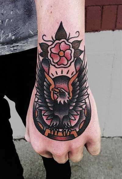 Tatuagem no pulso da menina - ferradura e a águia