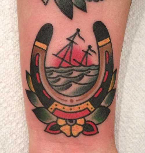 Tatuagem no pulso da menina - ferradura e barco