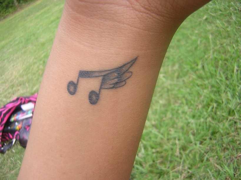 Tatuagem no pulso da menina - nota com asas