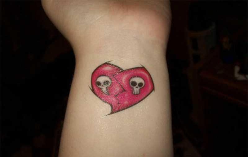 Tatuagem no pulso da menina - o coração com crânios