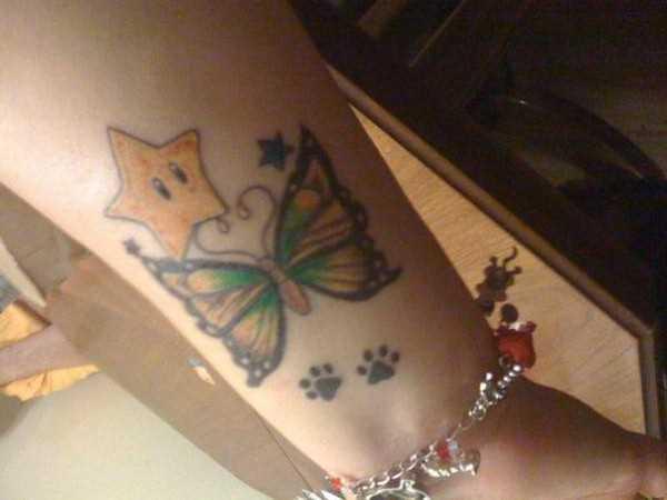 Tatuagem no pulso da menina - pata com um asterisco e uma borboleta