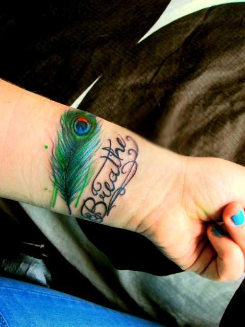Tatuagem no pulso da menina - pena de pavão