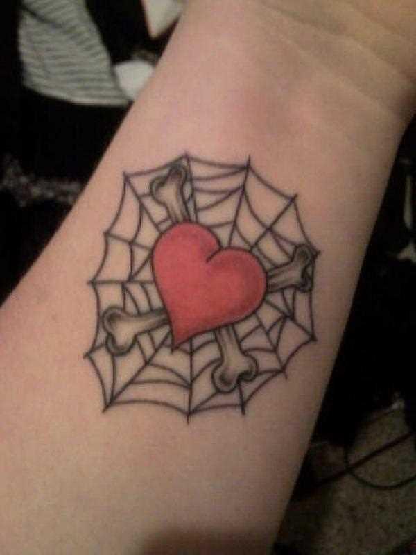 Tatuagem no pulso da menina - teia de aranha, o coração e os ossos