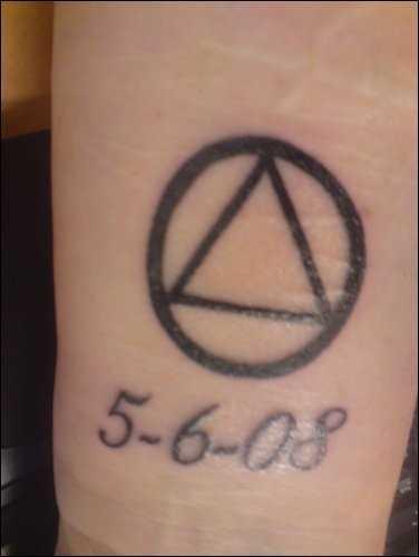 Tatuagem no pulso da menina - triângulo e a inscrição em data