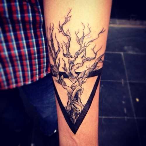 Tatuagem no pulso da menina - um triângulo e uma árvore dentro
