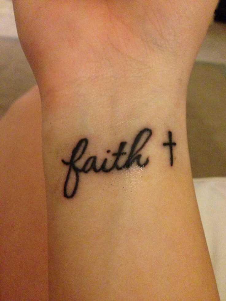 Tatuagem no pulso da menina - uma cruz com a inscrição