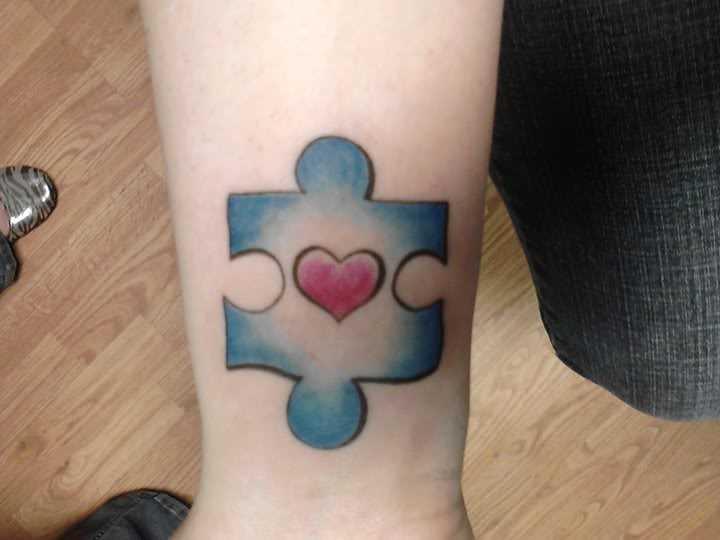 Tatuagem no pulso de uma menina de quebra - cabeça com o coração