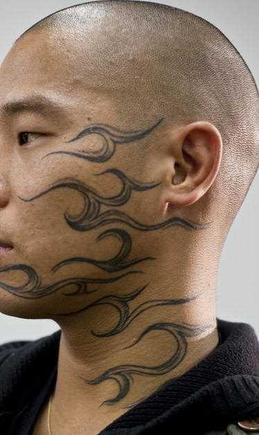 Tatuagem no rosto e no pescoço de um cara - chamas