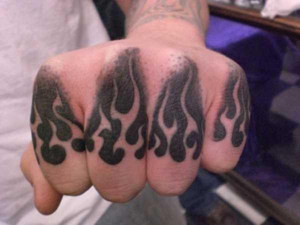 Tatuagem nos dedos de um cara - de- fogo