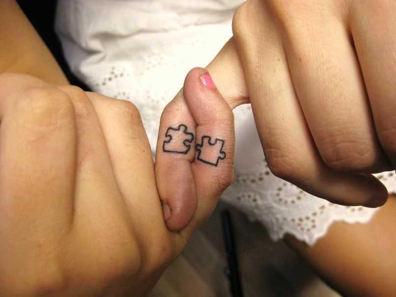 Tatuagem nos dedos de uma menina e um cara de quebra - cabeças