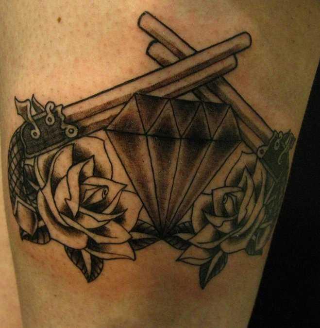 Tatuagem que a menina nos quadris em forma de pistola, de rosas e de um diamante