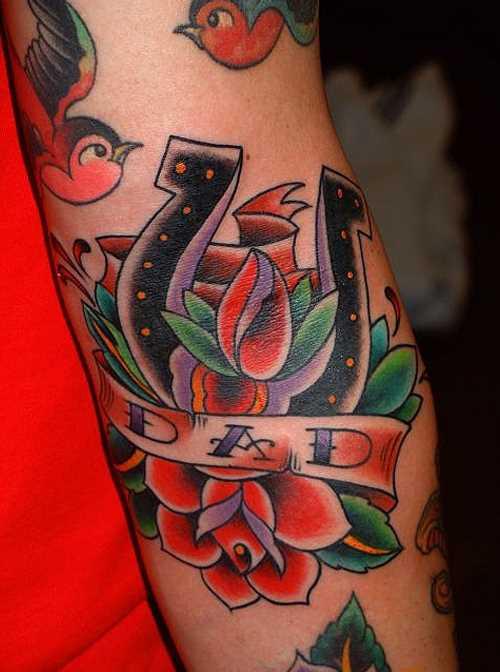 Tatuagem que tem no braço da menina - ferradura, rosa e inscrição