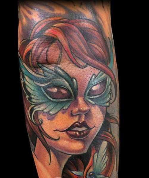 Tatuagem que tem no braço da menina - menina em uma máscara e uma borboleta