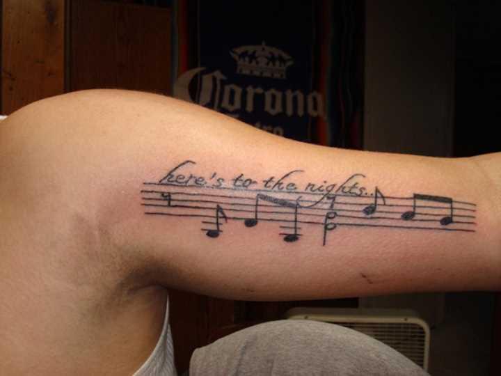 Tatuagem que tem no braço da menina notas e inscrição em anngliiskom
