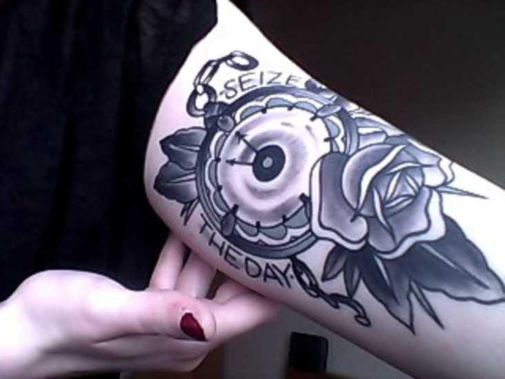 Tatuagem que tem no braço da menina - relógio com rosa