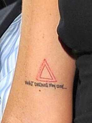 Tatuagem que tem no braço da menina - triângulo vermelho