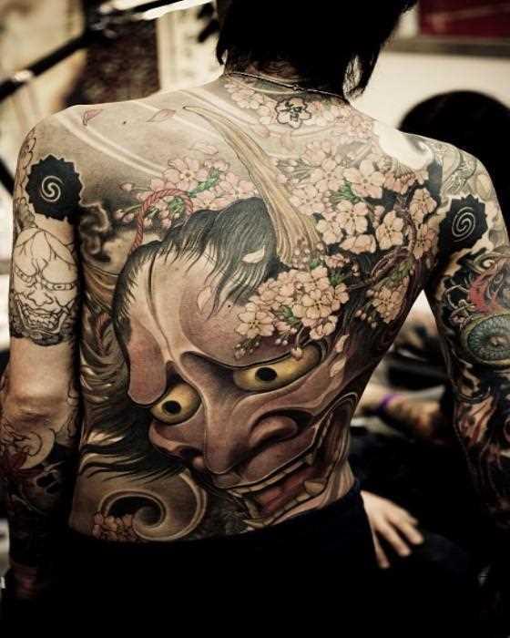 Uma grande tatuagem nas costas da menina - ímpios máscara e sakura