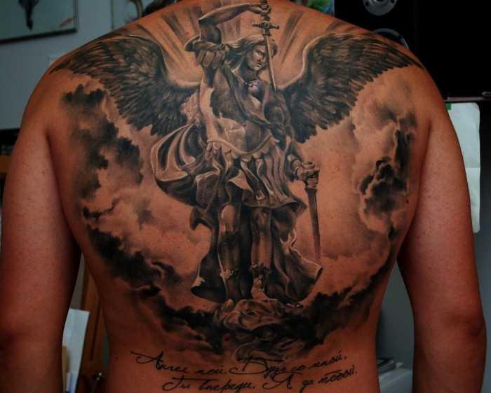 Uma grande tatuagem nas costas do cara - de- anjo com a espada