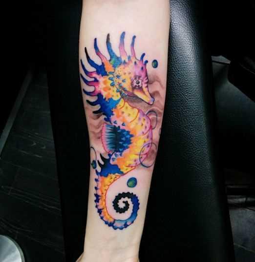 Uma imagem de cor do cavalo-marinho no antebraço da menina
