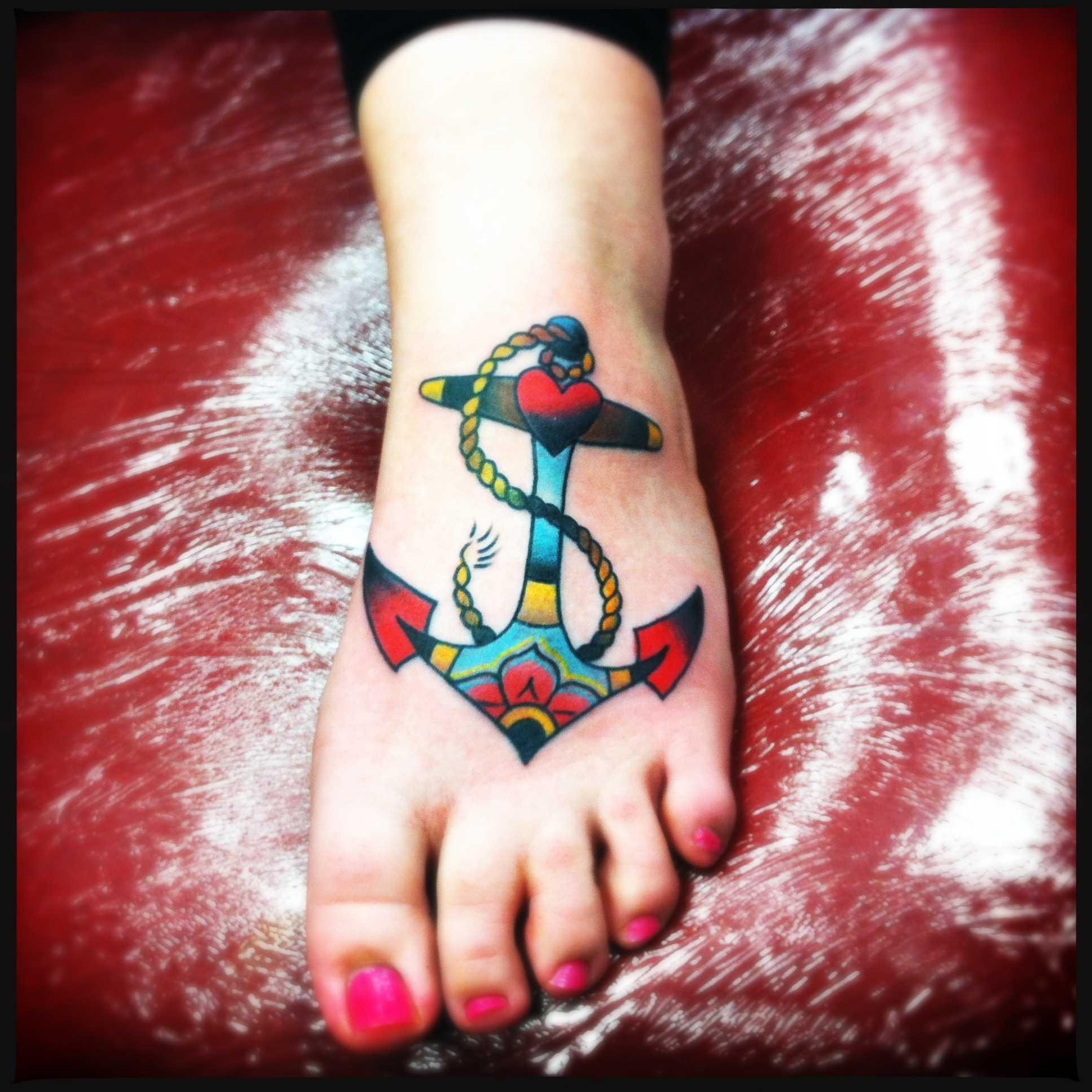 Uma tatuagem de âncora no estilo oldschool na planta do pé da menina