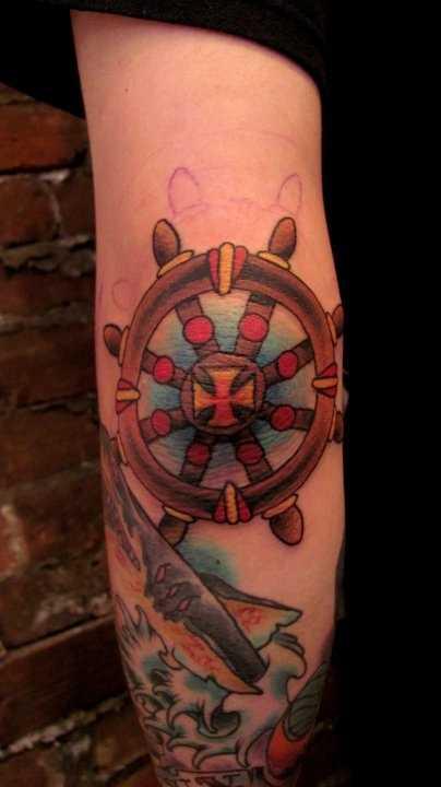 Uma tatuagem em forma de âncora oldschool no cotovelo do cara